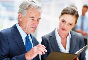 Senior man with female colleague going through a document